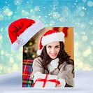 Composite image of festive brunette showing gift at christmas