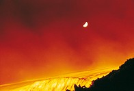 The lava going downhill while the volcano Etna erupting. In the sky, a shining moon. Sicily, May 1964