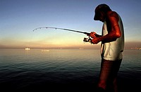 Fisherman fishing in Manila Bay. Roxas Boulevard. Manila. Philippines. Roxas Boulevard is a popular waterfront promenade in Manila in the Philippines....