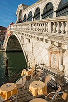 Rialto bridge over Grand canal and Chairs with tables in a sunny day in Venice, Italy.