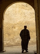 Silhouette of man walking through an archway in Fez, Morocco.