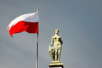Gdansk Poland. Polish flag and statue on top of The Court of Artus in the Old Town main street of Dlugi Targ.