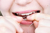 Close up on a young woman flossing her teeth perfect for dentistry, health and hygiene.