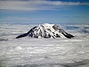 Mt. Rainier above the clouds. Rainier is the tallest mountain in th state of Washington about 55 miles southeast of Seattle. Mt. Rainier´s peak is 14,...