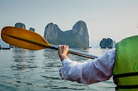 Woman kayaking at Halong Bay, Vietnam.