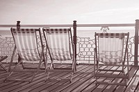Deck Chairs on Brighton Pier, England, UK in Black and White Sepia Tone.