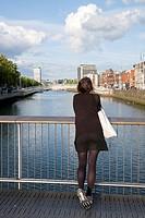 Young Woman on Millennium Bridge looking towards Ha´Penny Bridge, Dublin, Ireland.