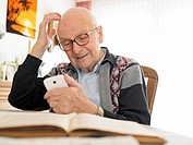Old man sitting at table using cell phone