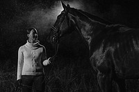 Woman and horse together in the rain, horizon format