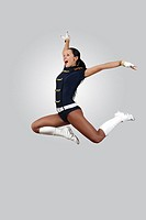 Young female dancer jumping against white background