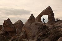 Woman walking near the fairy chimneys and rock formations in Goreme, Cappadocia Region, Nevsehir, Central Anatolia,Turkey, Europe.