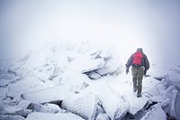 Russia, Hiker climbing over icy rocks in blizzard