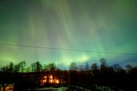 rural house with full sky canopy of northern lights aurora borealis near tromso in northern norway europe.