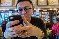 """Berlin, Germany, Chinese Tourist Inside, German Cusine Restaurant, """"""""Joseph Roth Diele"""""""", Sending Text Message Holding Iphone, Smart Phone at Table"""