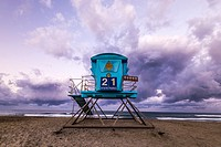 Blue colored lifeguard tower on Ponto Beach with storm clouds. Carlsbad, California, United States.