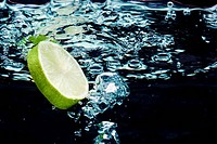 Slice of lime (lemon) falling in water near surface