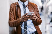 Businessman with smartphone and earphones hearing music on the subway train