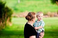 A mum cuddles her little boy in an outdoor green field.