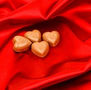 candy hearts on red satin background