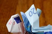 Twenty and ten euro bills crumpled on wooden table