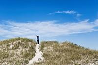 Woman affirms the new day, Dennis, Cape Cod, Massachusetts, USA.