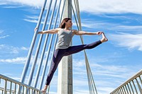 Extended hand to big toe yoga pose performed on a bridge, San Diego, California.