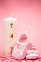 Pink baby booties with christening candle