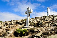 Cross for a victim of a shipwreck and the lighthouse of Laxe - death coast, Galicia Spain.