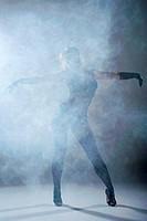 Woman dancing in a smoke. Studio