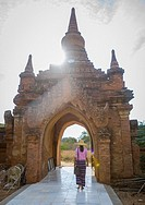 Woman Going Out Of An Old Temple Gate, Bagan, Myanmar.