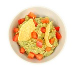 Guacamole dip with tortilla chips isolated over white background