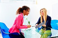 businesswomen interview meeting multi ethnic africand and blond sitting at office.