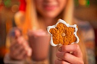 Closeup on teenage girl with cup of hot chocolate showing christmas cookie