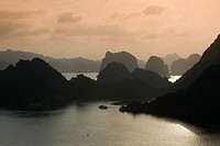 Boat on the water at sunset in the Ha Long Bay or Vinh Ha Long, limestone cliffs, UNESCO World Heritage Site, Gulf of Tonkin, North Vietnam, Vietnam