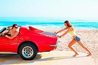 Girl pushing a broken car on the beach funny guy having fun.