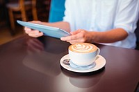 Close-up of digital tablet and coffee on table