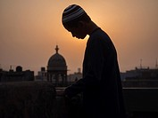Man on roof / building terrace and Minarets at sunset, New Delhi, India.