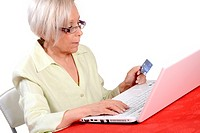 Elderly woman using her credit card to order a product online.