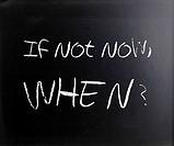 If not now, when? handwritten with white chalk on a blackboard.