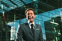 Laughing businessman outside office building