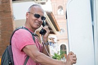 Tourist in Puerto Vallarta, Mexico. Man, 55 years old, hispanic ethnicity, carrying backpack, using public phone booth.