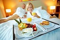 Older Caucasian couple eating breakfast on hotel room bed