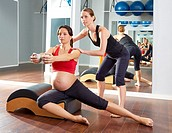 pregnant woman pilates side stretchs exercise workout at gym with personal trainer.