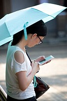 Young girl with umbrella and smartphone