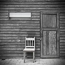 Old chair in front of old door, vintage style.