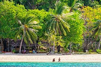 Two people sitting on the white sand beach at Banana Island, Coron, Palawan, Philippines.