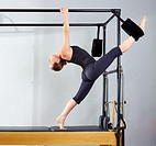 Pilates woman in cadillac split legs stretch exercise at gym.