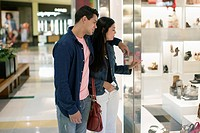 Couple looking through window display in shopping mall