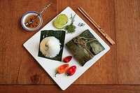 Roasted Salmon in Banana Leaves, spicy dill and lime paste, coconut rice, Vietnamese dipping sauce, peppers,.
