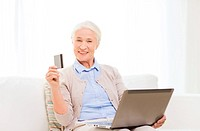 technology, age and people concept - happy senior woman with laptop compute and credit or bank card r at home